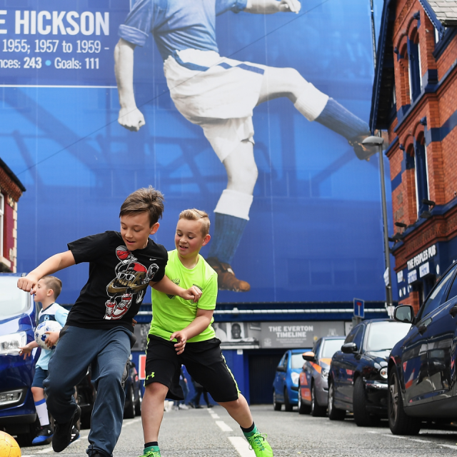 Two children play football in the street near Goodison Park
